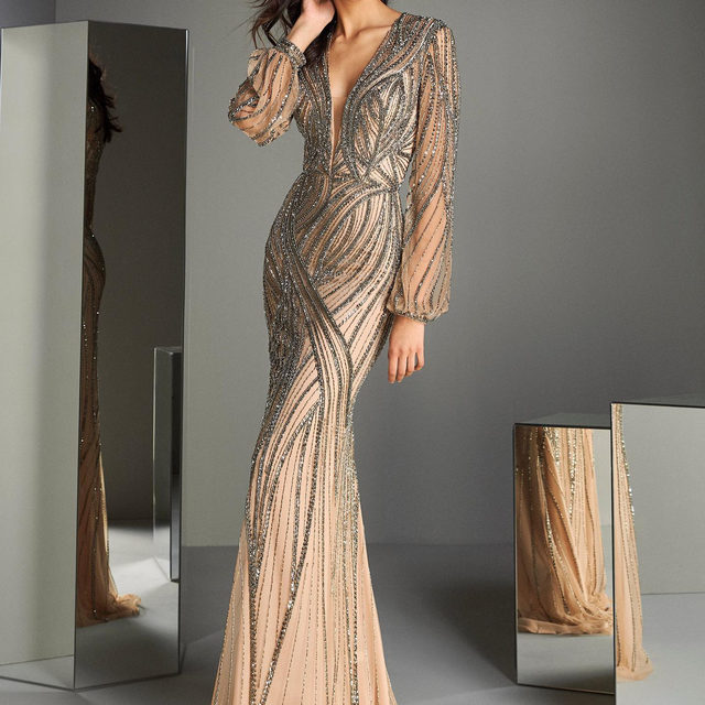Do you want to shine in a special event? The ATOS STYLE 47 is a stunning gown in nude tulle with extravagant, silver embroidery in dramatic streams that trace the flounce sleeves, plunge neckline, and fitted skirt for an ultra-flattering finish. #ThePartyEdit Collection. Link in bio to discover The Party Edit Collection
