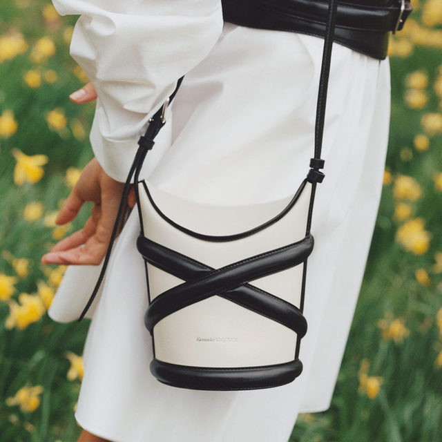 """IN THE BAG: Described by @alexandermcqueen's Sarah Burton as """"a strong and modern interpretation of the bucket bag,"""" the 'Curve' is inspired by the house's iconic harness  Tap the link in bio to shop at #NETAPORTER"""