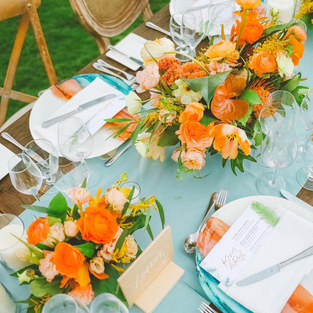 Quickly becoming one of our favorites, we cannot get enough of this color pairing! 🧡 The cool tone of the oceanic turquoise perfectly balances the warm hue of the fiery orange. Paired here with hues of peach and yellow. :chef's kiss: Featuring our Nile Blue Lamour Runner, White Hemstitch Napkin, and Horizon Charger. Use the link in our bio to see more of these marvelous products.  _________ Credits: Planner: @goldleafevent Photography: @angiediazphotography Floral: @mandygracedesigns Rentals: @inspirationhawaii Venue: @fslanai