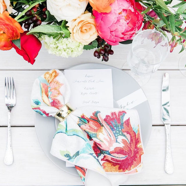 Colorful florals and matching napkins for the win! 💐 If you're opting for rustic farm tables, utilizing a colorful napkin is a great way to add that extra wow factor and still showcase the charm of the table. It's also a great budget-friendly alternative. Featuring our Biscayne Napkin. Use the link in our bio to see all of our colorful options!  _________ Credits: Planner: @michellegaribayevents Photography: @carriemcguirephoto Floral: @tre_fiori_floral_studio Rentals: @rusticurbanevents,@sigpartyrentals Paper Goods: @sea.and.sun.calligraphy Venue: @tciweddings